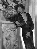 Claudette Colbert Leaning on Statue  wearing Black Dress