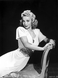 Carole Landis wearing Dress and sitting on Couch