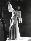 Loretta Young posed in Long Sleeve Dress on a Tree