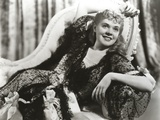 Alice Faye Lying on the Couch wearing a Dress