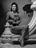 Joan Crawford sitting on a Wall Pillar in Classic