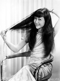 Anna Wong sitting on a Chair and Fixing Her Hair