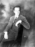 John Barrymore sitting on a Chair with Legs Crossed