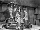 Maria Montez sitting on Snake Statue with Woman