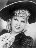 Mae West smiling in Glamorous Dress with Hat