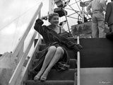 Anne Baxter on a Coat and sitting on a Stair