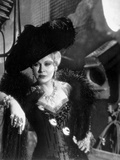 Mae West Leaning in Black Dress with Black Hat