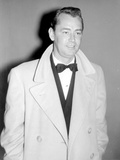 Alan Ladd standing  wearing a Long Coat