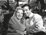 Alice Faye with a Guy sitting on a Becnh