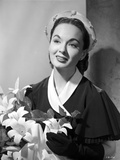 Ann Blyth Carrying a Flowers and smiling
