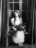 Mary Pickford sitting and Carrying Flowers