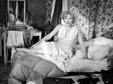 Anne Baxter sitting and posed on a Bed