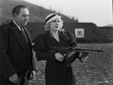 Mae West Holding a Gun with Man Behind Her