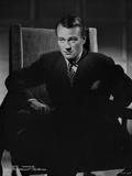 John Wayne sitting in suit and tie