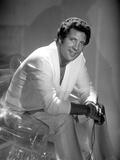 Tom Jones sitting in White Suit