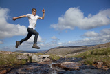 Boy (Aged 17) Jumping across Upland Stream
