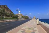 Man Wearing Dishdasha Walks Along Mutrah Corniche with National Flags  Middle East