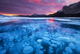 Bubbles and Cracks in the Ice with Kista Peak in the Background at Sunrise  Alberta  Canada