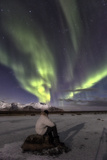 Man Sitting on Rock and Watching the Polar Light  at Night