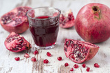 Pomegranates and Glass with Pomegranate Juice on White Wooden Table