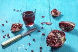 Sliced Pomegranate and a Glass of Pomegranate Juice on Turquoise Wooden Table