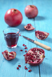 Whole and Sliced Pomegranate and Glass of Pomegranate Juice on Turquoise Wooden Table