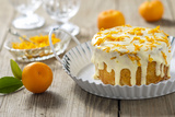 Small Orange Cake with White Icing on Wooden Table