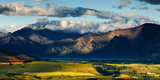 The Plains and Lakes of Otago Region Framed by Cloud Capped Mountains  Otago  South Island