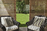 Colonial-Style Rattan Furniture with Striped Cushions in Decked Seating Area
