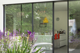 View from Garden Through Sliding Patio Doors to Modern Kitchen Beyond  London