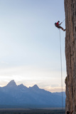 Climber Rappelling Down Boulder