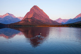 A Kayaker on Swiftcurrent Lake Watches the Sunrise over Mount Grinnell