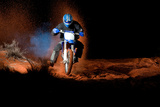 A Motorcyclist Rides on Sand Dunes  with Clouds of Sand and Smoke Behind Him