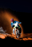 A Motorcyclist Rides on Sand Dunes  Kicking Up Sand Behind Him