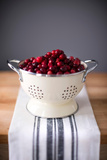 Bright Red Cranberries in Cream Colored Strainer Sitting on Vintage Striped Linen on Butcher Block