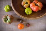 Variety of Heirloom Tomatoes in a Rustic Bowl and on a Light Wood Surface