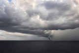 Tornado Touching Down at Sea with Dark Clouds Swirling
