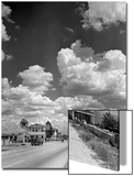 Cumulus Clouds Billowing over Texaco Gas Station along a Stretch of Highway US 66 Acrylique par Andreas Feininger