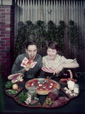 Teen Couple Eating Pizza from a Garden Table  1960
