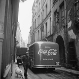 A Man Walks His Dog Beside a Bus with Coca Cola Advertisement  France  1950