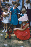Young Girl in a Bonnet and a Red Dress Feeding an Organ Grinder's Monkey  Iowa State Fair  1955