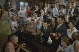 Low-Angle View of a Group of People as They Sing Along with a Pianist in a Unidentified Bar  1959