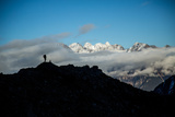 A Mountaineer Stands on a Mountaintop with Higher Peaks Visible in the Sunlight Beyond