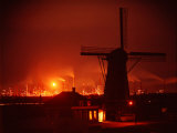 Lights and Fires of Pernis Refinery Glowing Behind Silhouetted Windmill