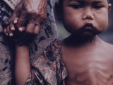 Close-Up of an Indonesian Child Holding on to the Hand of His Mother