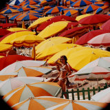 Europe Beach Scene Crowded with Colorful Umbrellas and a Bikini-Clad Young Woman