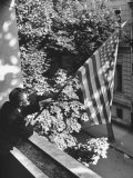 Man Hanging the American Flag Out of the Osteopath's Office Window During WWII