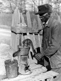 Old African American Sharecropper Dave Alexander Using Water Pump to Draw Water