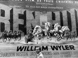 Actor Charlton Heston Posing in Front of Billboard of Film  Ben Hur