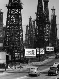 Car Traffic on Highway Next to Advertising Billboards and Oil Well Towers, Signal Hill Oil Field Papier Photo par Andreas Feininger